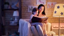 Le fasce orarie per risparmiare energia. Mamma che legge fiabe alla bambina sotto la luce fiocca di una lampada.
